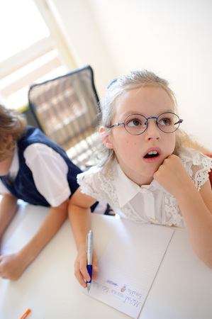 Small schoolgirl of an elementary school sits at a school desk in thoughtfulness. Girl rested her head on his hand and looking dreamily somewhere. Nearby sits her classmate. Stock Photo