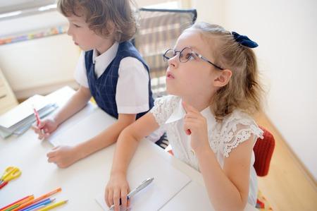 Dva malí žáci ze základní školy sedí u stolu. Na školním stole jsou učebnice a školní příslušenství. Chlapec se dívá na stranu. Školačka s brýlemi se zamyslela nad otevřenou knihou. Reklamní fotografie