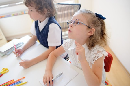 industrious: Two little disciples of an elementary school sit at desk. On a school desk there are textbooks and school accessories. Boy looking to the side. Schoolgirl with glasses pondered over an open copybook.