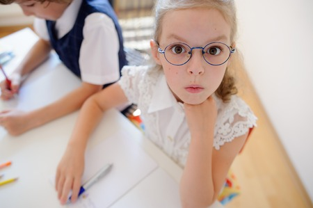 Dva mladí studenti základní školy sedí u stolu. Na stole jsou učebnice a školní potřeby. Chlapec něco píše. Školačka v brýlích pohledu do kamery s překvapením.