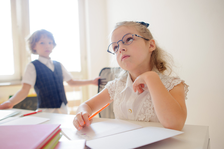 reverie: Cute petite schoolgirl in glasses sits at a desk in a reverie. Open copybook and school supplies are on the desk. Near the window is a classmate of girl.