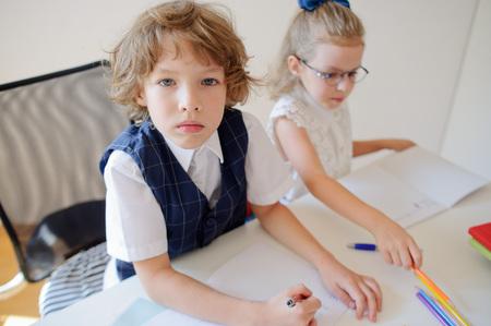 žák: Dvě malé žáky základní školy sedí ve školní lavici. Na lavici existují učebnice a školní pomůcky. Chlapec se dívá do kamery s vážným výhledem. Školačka píše něco. Reklamní fotografie