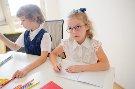 industrious: Two small disciples of an elementary school sit at desk. On a school desk there are textbooks and school accessories. Boy looking to the side. Schoolgirl with glasses pondered over an open copybook.