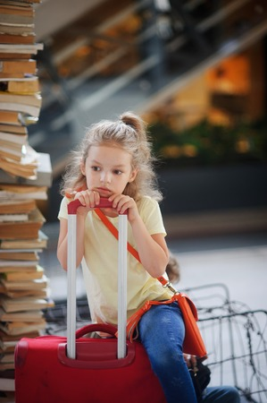 Charming girlie 7-8 years sits beside their luggage at the station. Girl pondered or tired. She sits, leaning on the handle of a suitcase. Tall stack of old books next to her.