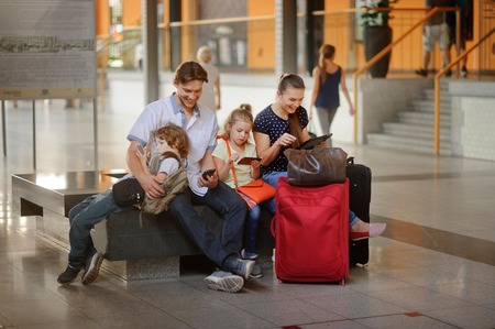 Young parents with two children at the railway station. Family in a large waiting room. All have settled down on a bench. Everyone looks in your gadget. Nearby are the suitcases and travel bags.