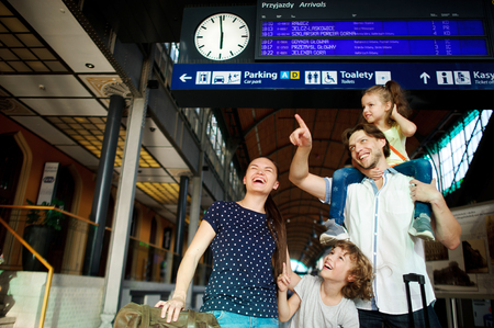 wherever: Cheerful young family at the train station. Father, mother, son and daughter are under an electronic scoreboard. Father holding small daughter on his shoulders. Everyone looks wherever shows father.