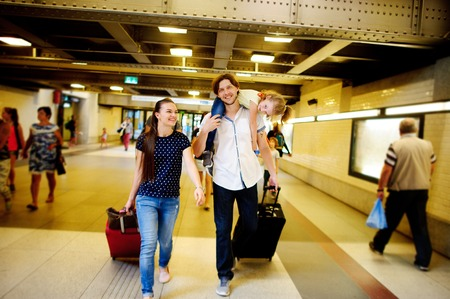 hasten: Young pair with a daughter hasten at train station. The man holds the daughter on shoulders. The husband and the wife roll behind itself suitcases. They are smiling happily.