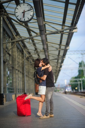 tenderly: Loving couple stands on the empty platform under the clock. A young man embraces a girl. They tenderly looking at each other. Nearby is a large red suitcase. In the distance, the approaching train.