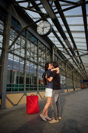 tenderly: Loving couple met or parted on an empty platform under the clock. The young man put his arm around the girl. They tenderly looking at each other.