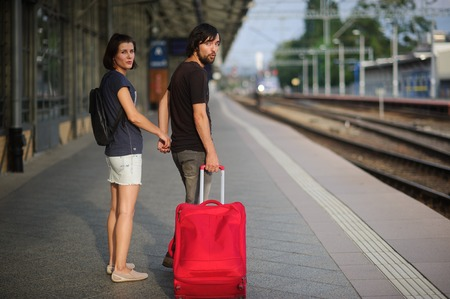 Young couple standing on the platform holding hands. Young man rolls the red suitcase. Both looking into the camera. Stock Photo
