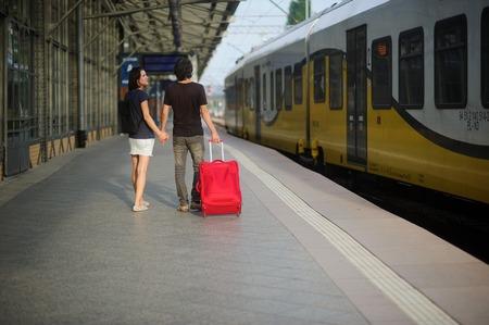 manos unidas: Los jóvenes costos de los pares en la plataforma que unieron sus manos. El joven lanza una maleta roja. Ambos se ven en el tren eléctrico acercado.