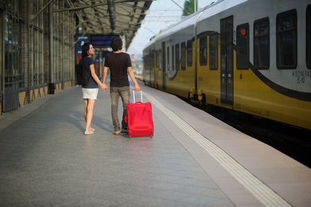 joined hands: The young pair costs on platform having joined hands. The young man rolls a red suitcase. Both look at the approached electric train.
