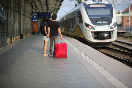 manos unidas: La joven pareja de pie en la plataforma que unieron sus manos. El joven lanza una maleta roja. Ambos se ven en un tren que se acerca.