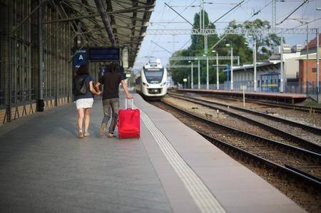 manos unidas: Los jóvenes costos de los pares en la plataforma que unieron sus manos. El joven lanza una maleta roja. Tanto apresurar en un tren que se acerca.
