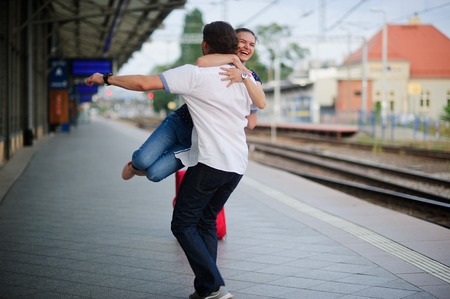 Joyful meeting at the railway station. The young man easily lifted the girl. She hugged him tightly. On a girls face happy smile. Stock Photo