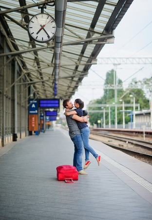 Joyful meeting at the railway station. The young man lifted the girl. Young people with tenderness look at each other. Nearby the red suitcase has fallen.