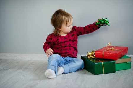 saint nick: The little girl in jeans and a sweater sits on a floor near bright boxes. The baby with interest examines boxes. Gifts on the occasion of some holiday. Happy birthday. Merry Christmas.Happy New Year