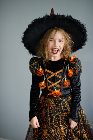 hallows: All Hallows Eve. Girl shows the evil sorceress. She is wearing a black-and-orange dress and hat. From under his hat sticking disheveled hair. The girl has an evil expression. Trick or Treat