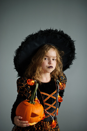 goodies: Portrait of the girl of 8-9 years in a suit for Halloween. She represents the evel sorcerer. The girl is dressed in a black-orange dress a hat. In hands at her pumpkin - Halloween symbol. Stock Photo