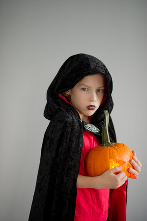 hallows: All Hallows Eve. Boy age dressed in a costume for Halloween. He represents the evil wizard. Boy is gowned in a black-red toga with a hood. He holds pumpkin with a candle inside - Halloween symbol. Stock Photo