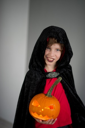 hallows: All Hallows Eve. Boy age dressed in a costume for Halloween. He represents the evil wizard. Boy is gowned in a black-red toga with a hood. He holds pumpkin with a candle inside - Jack o lantern Stock Photo