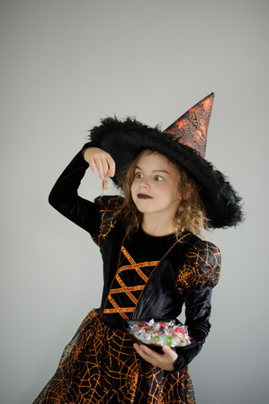 goodies: Halloween Party. Girl 8-9 years in image the evil sorcerer. On the girl a black-orange dress and a big hat. Girl holds sweets in hands. She has a ridiculous look. Trick or Treat.