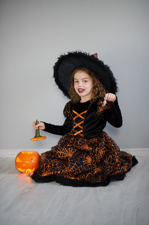 pretend: The beautiful girl of 8-9 years in image the evil fairy. The girl has dressed up by Halloween. In hands at her pumpkin with a candle inside - Halloween symbol.