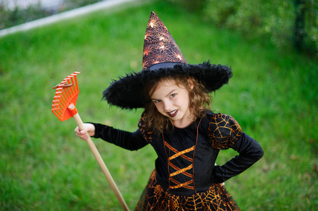 Preparation for Halloween. The girl in a suit of the evil witch cleans a lawn of rake. The girl is dressed in a black-orange dress and a big hat. She has a good mood. Children adore Halloween.