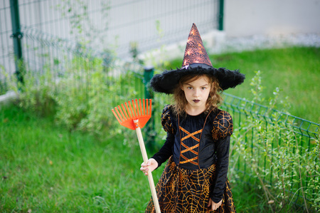 prank: Preparation for Halloween. The girl in a suit of the evil witch cleans a lawn of rake. The girl is dressed in a black-orange dress and a big hat. She has a good mood. Children adore Halloween.