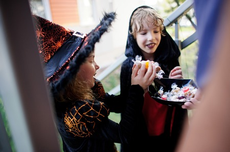 Two children, boy and girl, in dark costumes for Halloween take candies. In the foreground a hand with the vase filled with sweets.Trick or Treat. Children love Halloween.