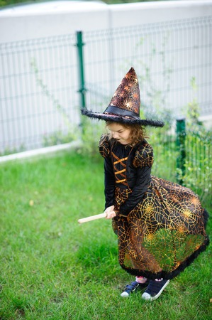 prank: Preparation for Halloween. The girl in a suit of the evil witch pretends that she flies on the broom. The girl is dressed in a black-orange dress and a big hat. She has a good mood. Children adore Halloween.