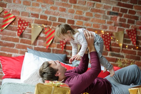 Christmas morning. Young man cheerfully plays with small daughter. On a bed there are many Christmas gifts in bright packings. The room is festively decorated. Merry Christmas and a Happy New Year. Stock Photo