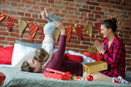 Christmas morning.Young family gleefully congratulates each other Marry Christmas.On bed there are many Christmas gifts in bright packings and Christmas-tree decorations.Merry Christmas.Happy New Year Stock Photo