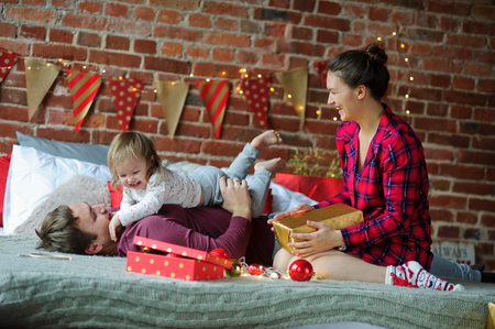 Christmas morning. Young family gleefully congratulates each other Marry Christmas. On a bed there are many Christmas gifts in bright packings. Dad playing with his little daughter. Stock Photo