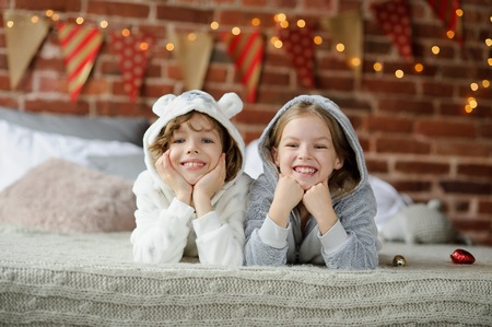 Christmas Holidays. Brother and sister lying on bed in pajamas. The bedroom is decorated with Christmas lights. In children a good mood. They are smiling happily. Merry Christmas and a Happy New Year.