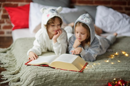 Christmas Holidays. Brother and sister lay on a bed in soft pyjamas. Bedroom is decorated by christmas garlands. Children thumb through the huge book with Christmas fairy tales. Merry Christmas. Stock Photo
