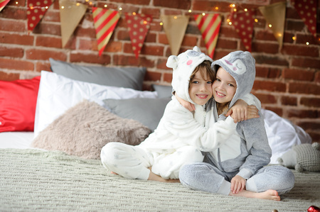 nikolay: Christmas. Two children in pajamas sitting on the bed waiting for Christmas gifts. The bedroom is decorated with festive garlands. Children happily embrace. Merry Christmas. Happy Christmas.