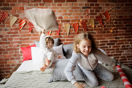 Christmas Holidays. Two children in soft pyjamas have arranged fight by pillows. The bedroom is decorated by christmas garlands. Children adore Christmas and cheerfully spend time. Merry Christmas.