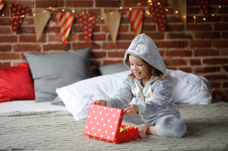 Christmas Holidays. Cute girl 8-9 years, sits on a bed with a box in his hands. She received a Christmas gift. Bedroom decorated with Christmas garlands. Children adore Christmas and Christmas gifts. Stock Photo
