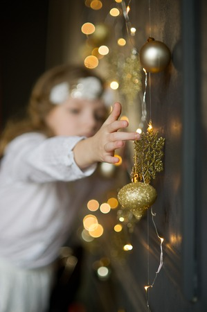Seasons Greetings. Girl of 8-9 years in white clothes with delight touches gold Christmas garlands and ornaments. They shine a magic light. Christmas-the mysterious and wonderful time. Merry Christmas Stock Photo