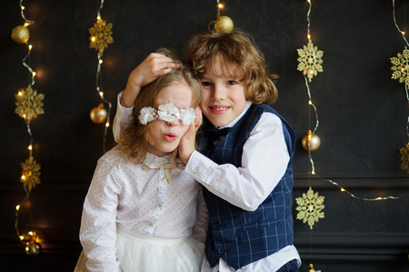 Christmas. Two festively dressed children photographed for Christmas card. Kids tired pose, they are acting up. Against the background of the dark walls, decorated with golden Christmas lights.