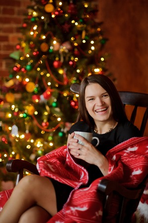 boxing day: Young woman sits in a rocking-chair having wrapped up with a plaid near Christmas-tree. She holds a cup in hand. Woman with pleasure has a rest. She smiles. The Christmas tree glow electric garlands.
