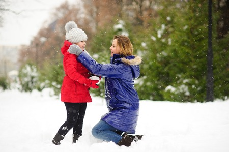 Young woman and her daughter builds snowman. Woman and girl are dressed in bright and warm jackets. It is snowing. Mom lovingly corrects daughters jacket. All earth is covered with fluffy snow. Stock Photo
