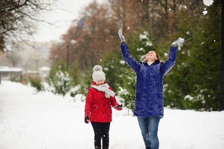 Young woman with the daughter on walk in winter day. Woman and the girl are dressed in bright down-padded coats. It is snowing. Ground in the park is covered with snow. Mother throws snow up. Stock Photo