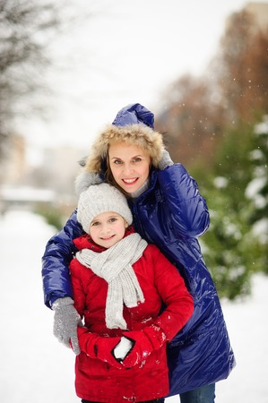 Mother tenderly embraces the daughter. Them well together The woman and the girl of school age are dressed in warm bright down-padded coats. It is snowing. The earth is covered with snow.