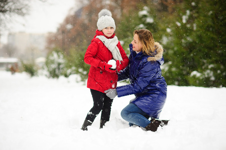 lovingly: Young woman and her daughter builds snowman. Woman and girl are dressed in bright and warm jackets. It is snowing. Mom lovingly corrects daughters jacket. All earth is covered with fluffy snow. Stock Photo