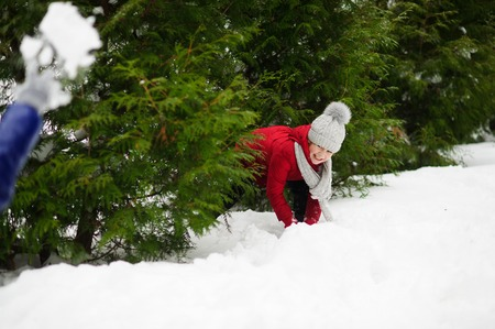 rival: Cheerful girl of school age in a red jacket plays with someone in snowballs. She hides in bush thickets from the rival. Ground is completely covered with fluffy snow. Game gives to the child pleasure.