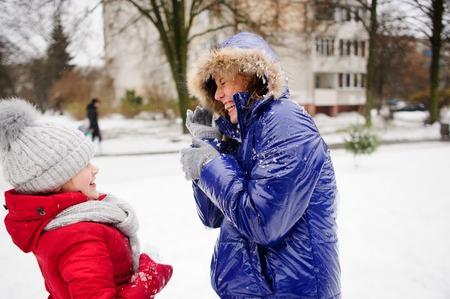 palle di neve: La donna si trasforma a parte le palle di neve che volano a lei. Figlia spara ai suoi palle di neve. La donna ha esposto le mani in avanti e ride allegramente. Tutti a terra è completamente coperto di neve soffice.