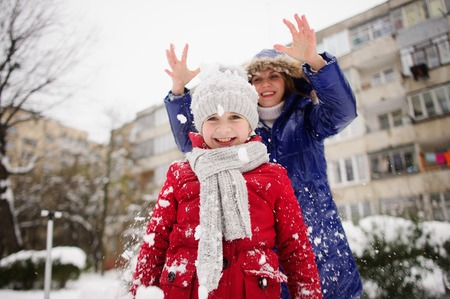 cheerfully: Mother with daughter cheerfully spend time in winter day. They are dressed in warm bright down-padded coats. Mother pours snow on the head of the daughter. Both cheerfully laugh.