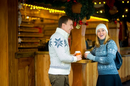 good time: Eve of Christmas. Cute young couple has a good time at the Christmas bazaar. Young people stand near a wooden counter with paper cups in hands. Stall is festively decorated with wreaths and garlands.